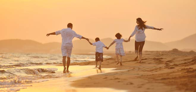 Family Running down the beach at sunset