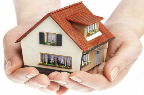 Hands holding a miniature house