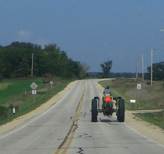 John Deer tractor driving on the road