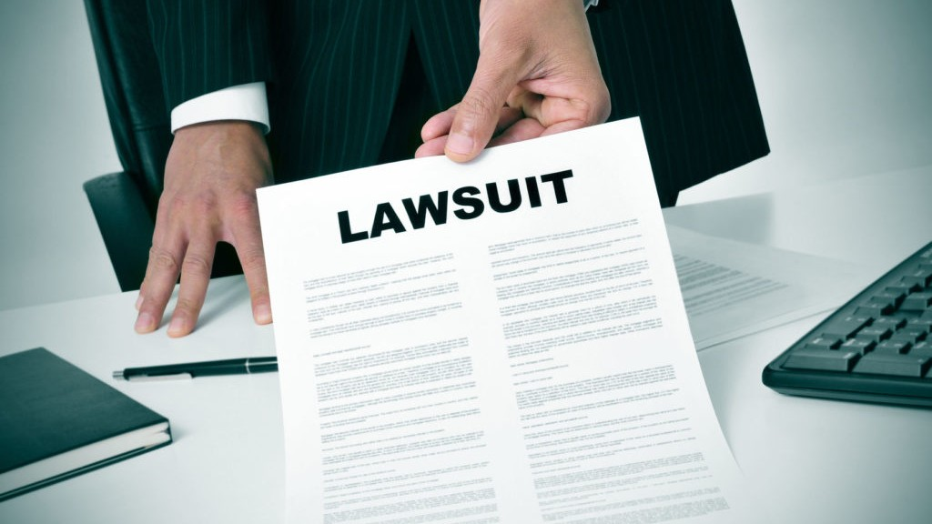 27915554 - a lawyer in his office showing a document with the text lawsuit written in it